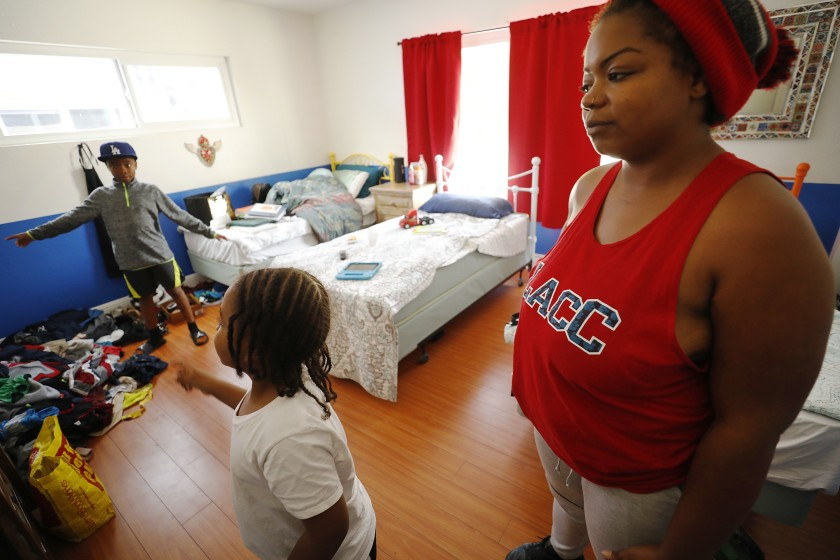 Anna Gray, and her children, Harold Germany, 9, and Patrick Hunt, 5, are seen during the summer of 2019 at a recently opened temporary shelter located on West 3rd Street in Los Angeles that is reserved for single women and families. She shares the room with her sons. (Credit: Al Seib / Los Angeles Times)