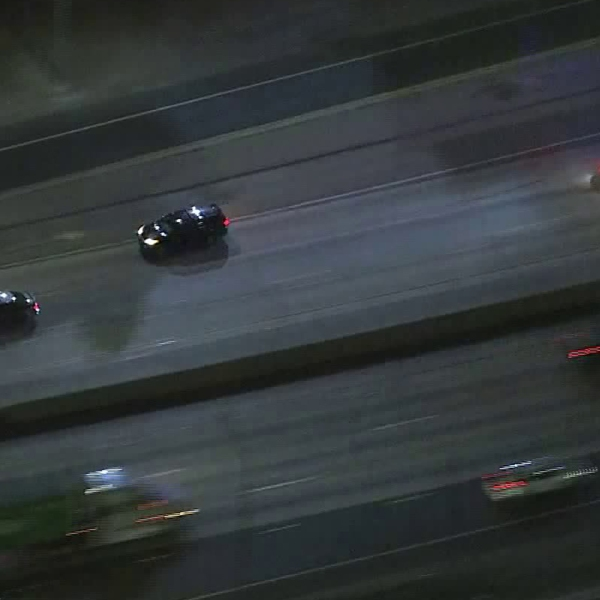 Law enforcement officials pursue a fleeing car along the 405 Freeway in West L.A. on July 2, 2019. (Credit: KTLA)