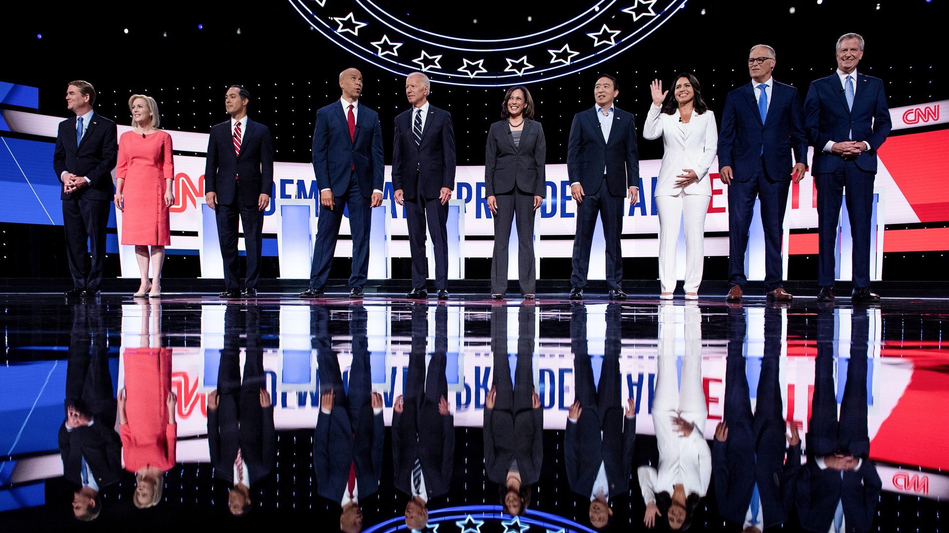 From left: Democratic presidential hopefuls Sen. Michael Sen. Kirsten Gillibrand of New York, former U.S. Secretary of Housing and Urban Development Julian Castro, Sen. Cory Booker of New Jersey, former Vice President Joe Biden, Sen. Kamala Harris of California, entrepreneur Andrew Yang, Rep. Tulsi Gabbard of Hawaii's 2nd District, Washington Gov. Jay Inslee and New York City Mayor Bill de Blasio arrive on stage ahead of the second round of the second Democratic primary debate of the 2020 presidential campaign season hosted by CNN in Detroit on July 31, 2019. (Credit: Brendan Smialowski / AFP / Getty Images)