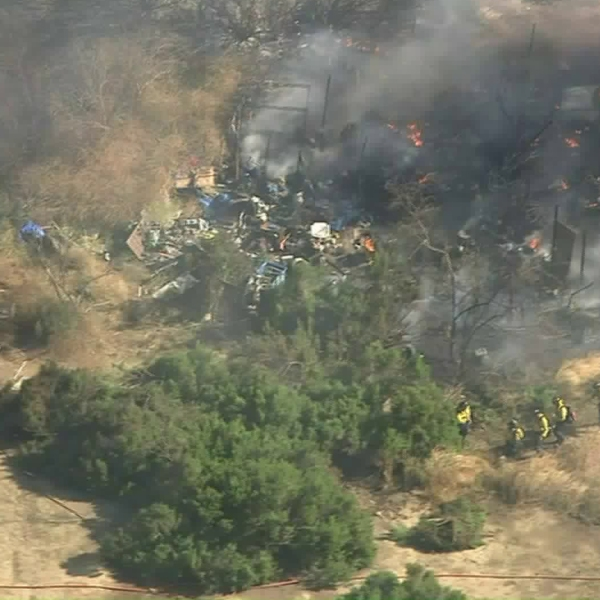 Firefighters respond to a homeless encampment during a brush fire in the Sepulveda Basin on July 30, 2019. (Credit: KTLA)