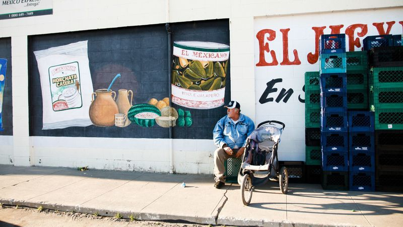 An undated image shows a man sitting outside a grocery store in Firebaugh, a rural farming community with a population of about 7,000 people, has struggled with higher unemployment than many other parts of California. (Credit: Bethany Mollenkof / Los Angeles Times)