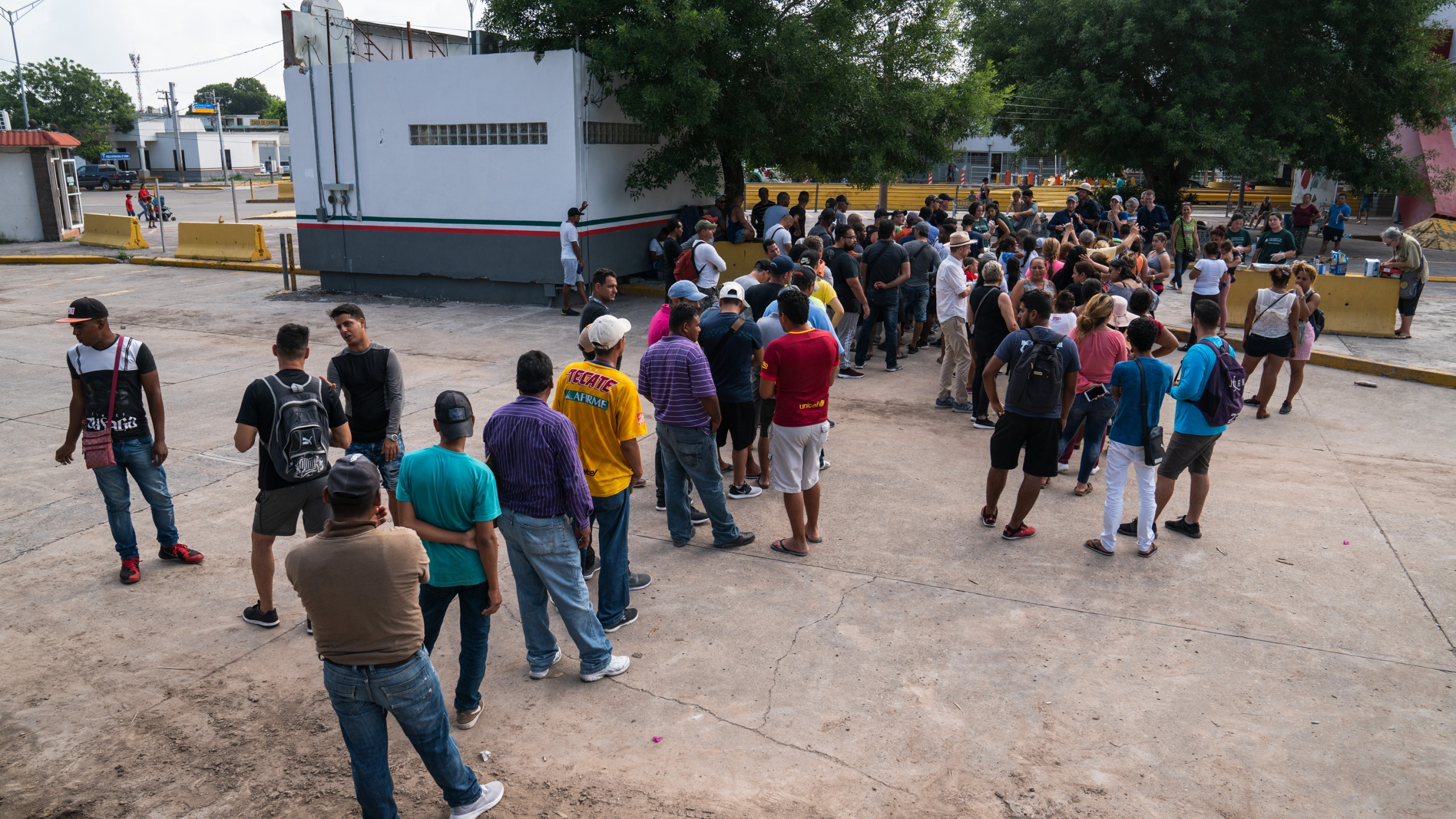 Asylum-seekers wait in line to get a meal close to the International Bridge near a section where a father and daughter drowned attempting to cross into the United States on June 26, 2019 in Matamoros, Tamaulipas. (Credit: Verónica G. Cárdenas/Getty Images)