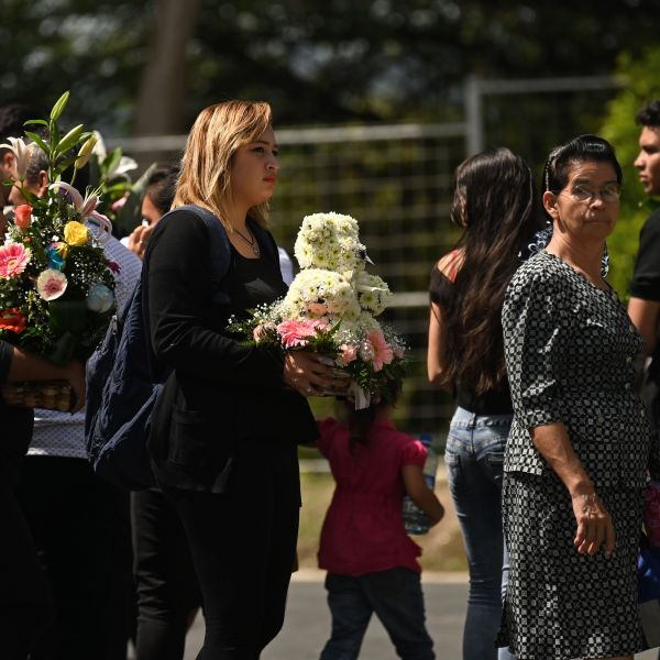 People attend the funeral of Salvadoran migrant Oscar Martinez and his almost two-year-old daughter Angie Valeria, who both drowned while trying to cross the Rio Grande from Mexico to the United States, at La Bermeja cemetery in San Salvador on July 1, 2019. (Credit: Marvin Recinos/AFP/Getty Images)