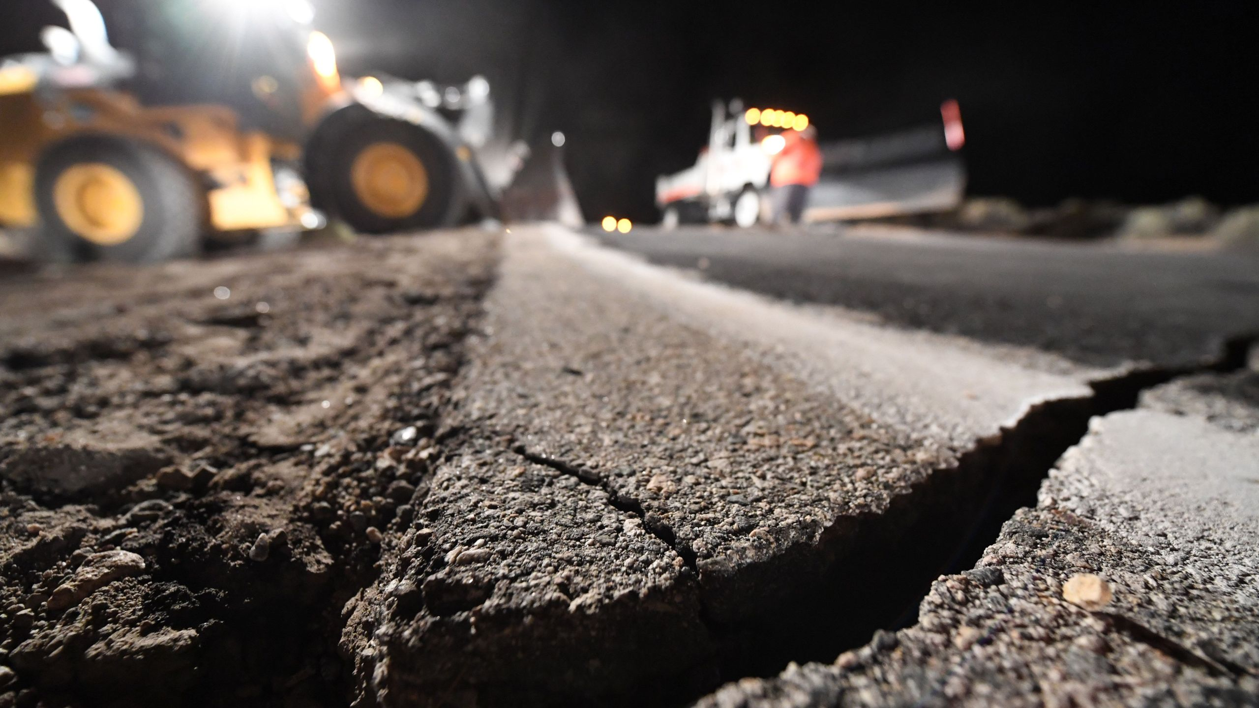 Highway workers repair a hole that opened in the road as a result of the July 5, 2019 earthquake, in Ridgecrest, California. (Credit: ROBYN BECK/AFP/Getty Images)