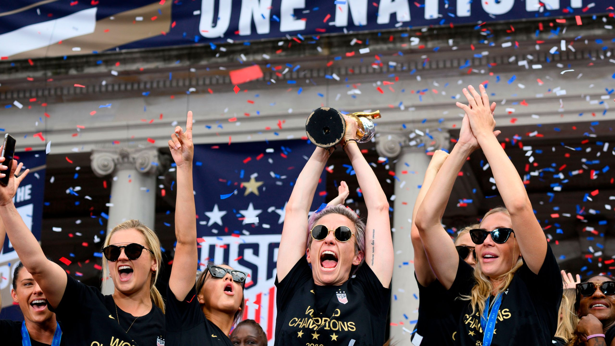 Megan Rapinoe and her team members celebrate with the trophy in front of the City Hall after the ticker tape parade for the women's World Cup champions on July 10, 2019 in New York. (Credit: JOHANNES EISELE/AFP/Getty Images)