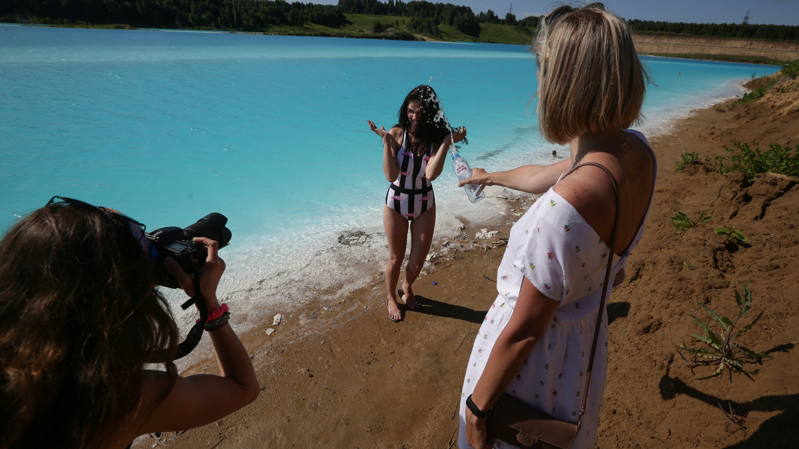 """A young woman poses for pictures by a Novosibirsk energy plant's ash dump site that has been nicknamed """"Maldives"""" by locals on July 11, 2019. (Credit: Rostislav Netisov/AFP/Getty Images)"""