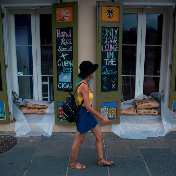 A woman walks past a cigar lounge and bar lined with sandbags in New Orlean's French Quarter ahead of the arrival of Tropical Storm Barry on July 11, 2019. (Credit: Seth Herald / AFP / Getty Images)