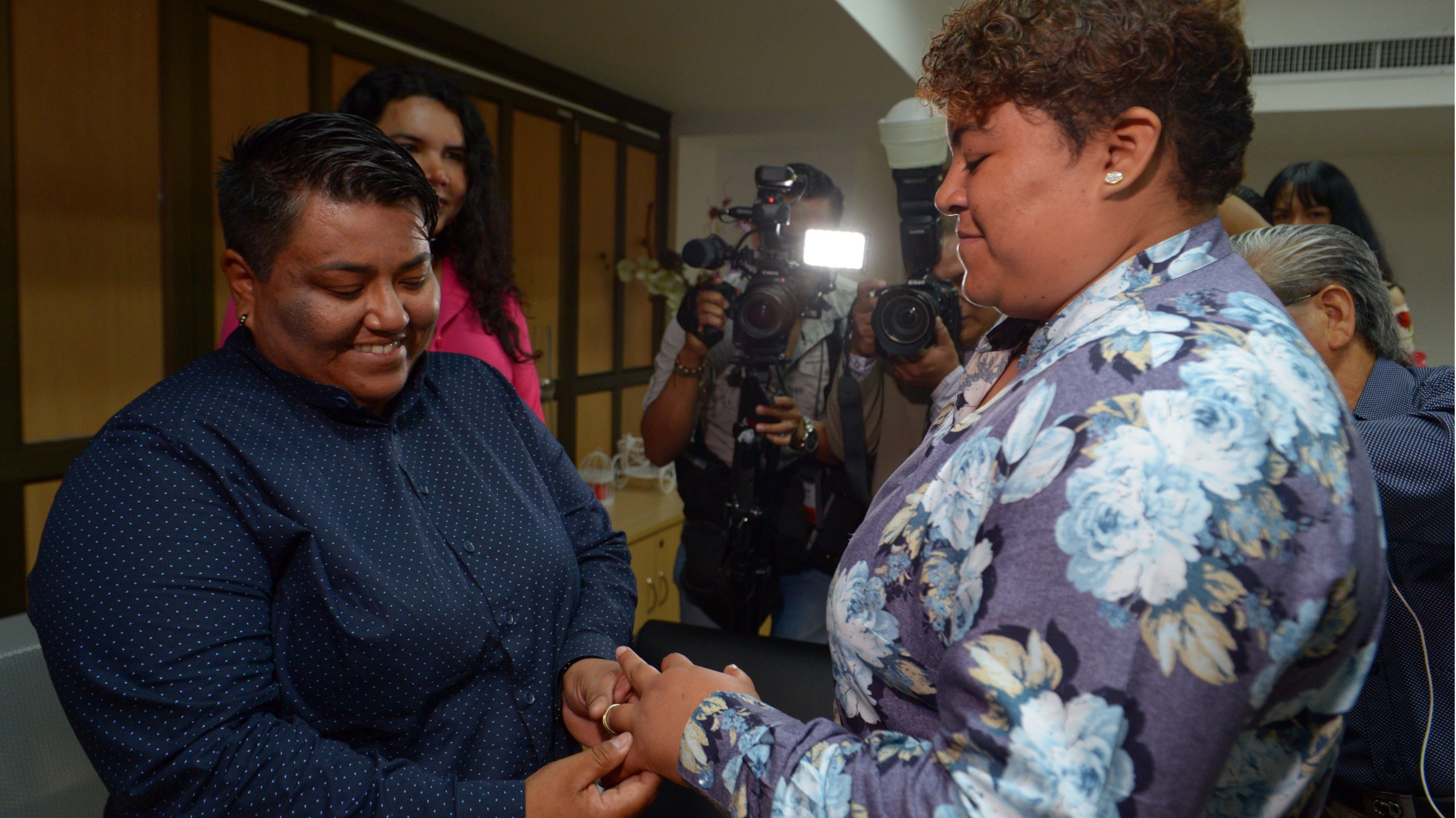Alexandra Chavez (left) places a ring on the finger of Michelle Aviles during Ecuador's first same sex marriage at a registry office in Guayaquil on July 18, 2019. (Credit: MARCOS PIN/AFP/Getty Images)