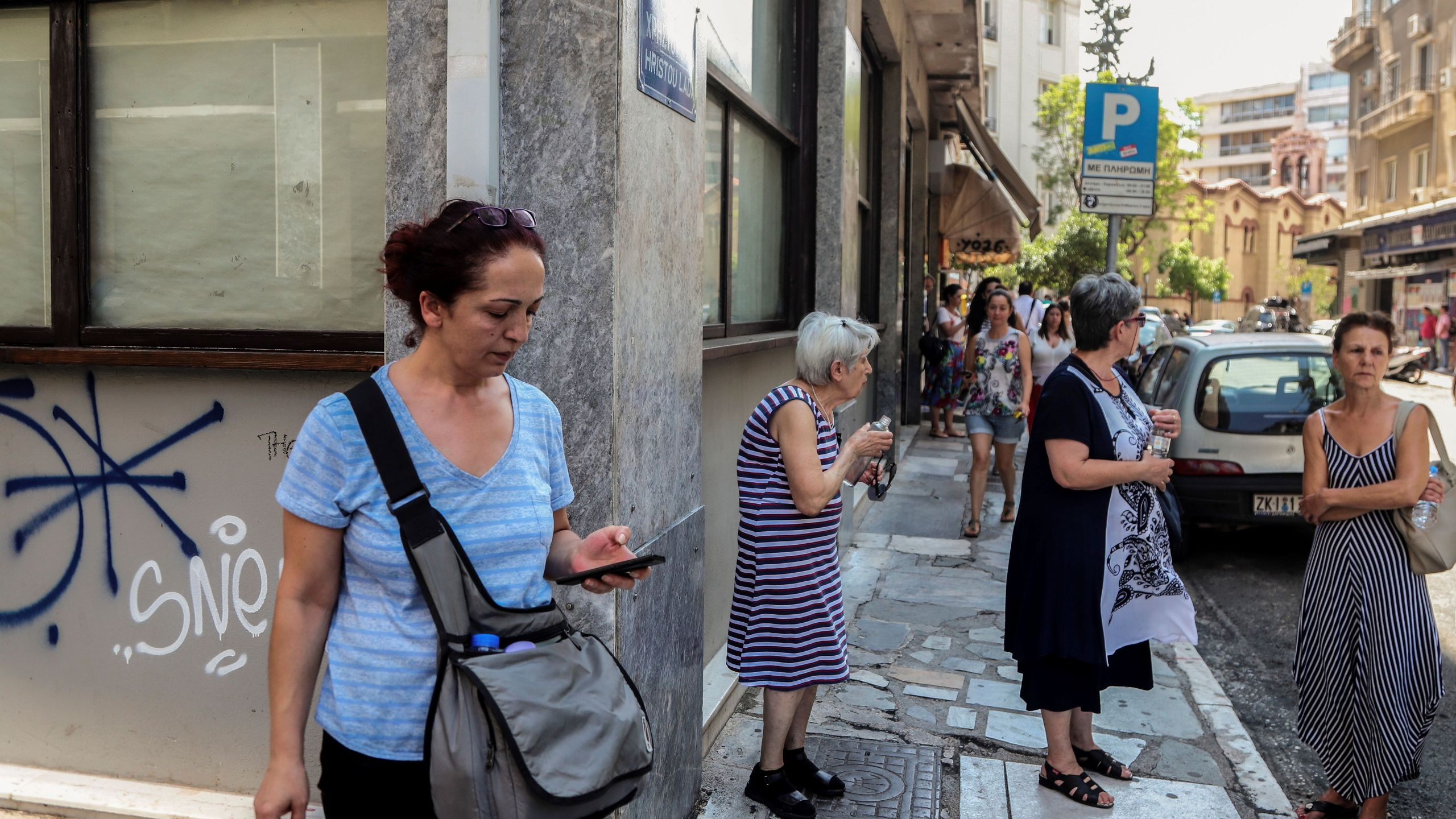 People stand outside buildings in central Athens after an earthquake on July 19, 2019. (Credit: EUROKINISSI/AFP/Getty Images)