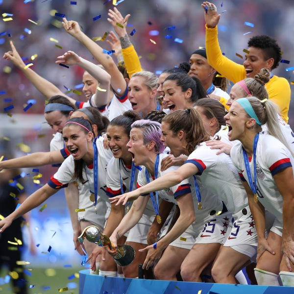 Megan Rapinoe lifts the FIFA Women's World Cup trophy following her team's victory in the 2019 FIFA Women's World Cup final on July 7, 2019 in Lyon, France. (Credit: Alex Grimm/Getty Images)