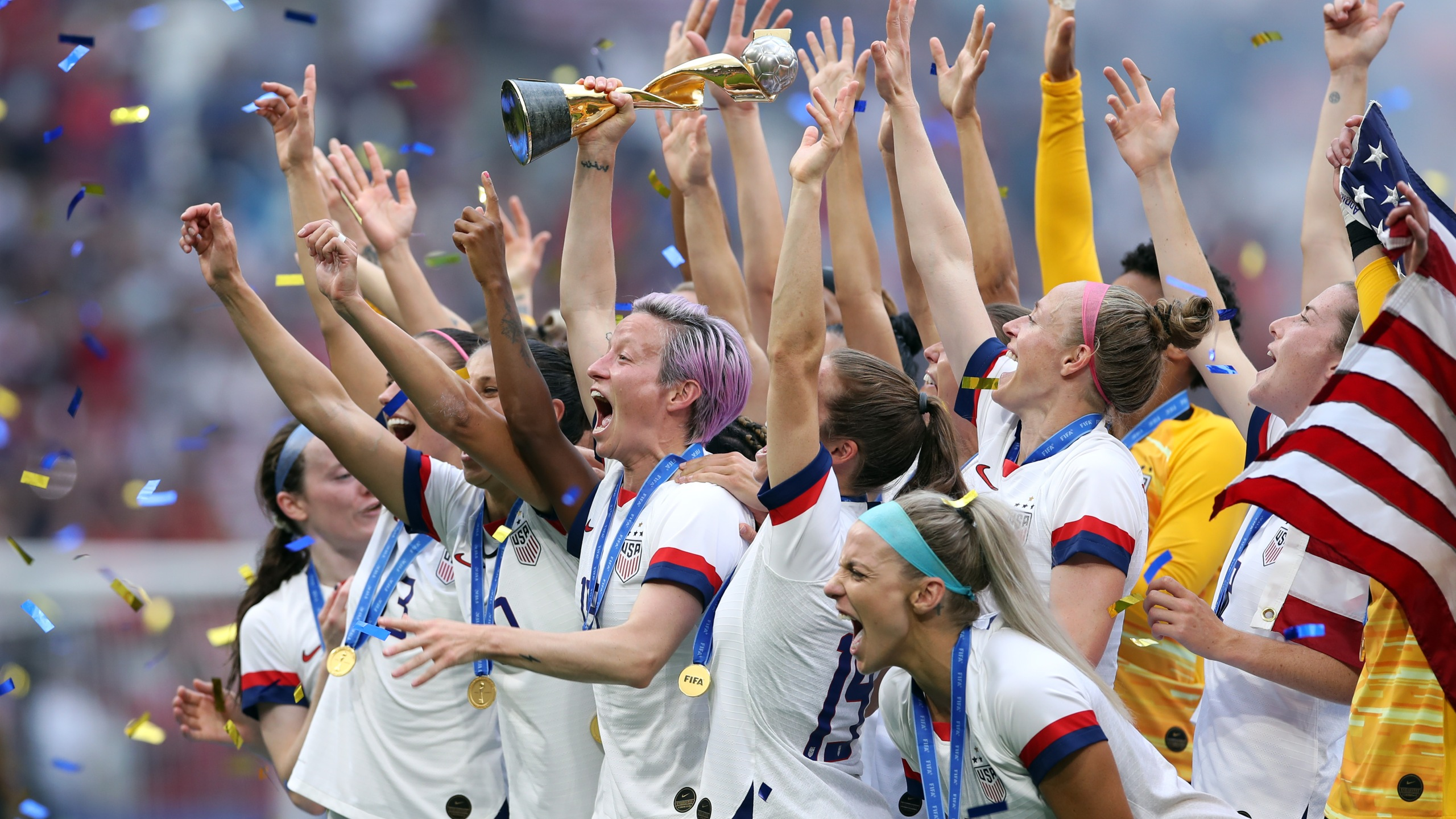 Megan Rapinoe of the USA lifts the FIFA Women's World Cup Trophy following the US victory in the 2019 FIFA Women's World Cup France Final. (Credit: Alex Grimm/Getty Images)