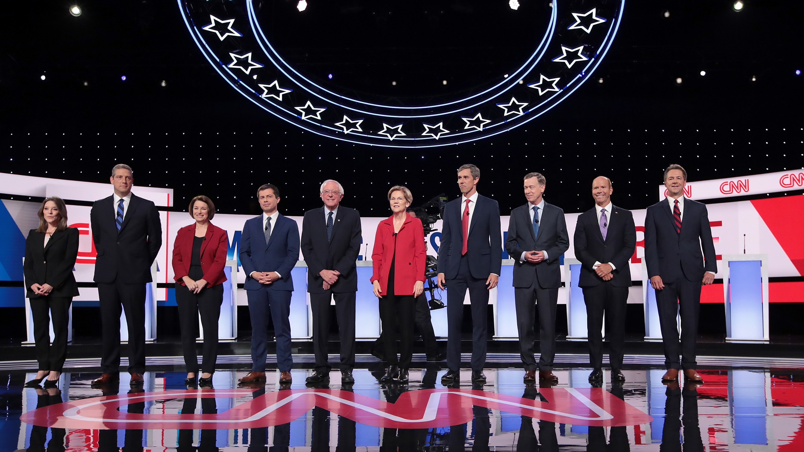 From left: Democratic presidential candidates Marianne Williamson, Rep. Tim Ryan, Sen. Amy Klobuchar, Indiana Mayor Pete Buttigieg, Sen. Bernie Sanders, Sen. Elizabeth Warren, former Texas congressman Beto O'Rourke, former Colorado governor John Hickenlooper, former Maryland congressman John Delaney and Montana Gov. Steve Bullock take the stage at the beginning of a CNN-hosted in Detroit on July 30, 2019. (Credit: Scott Olson / Getty Images)