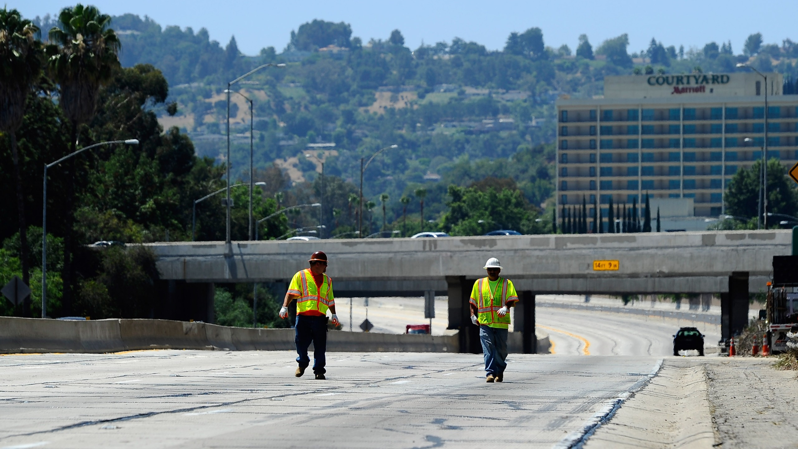Construction workers walk on the empty southbound lanes of the 405 Freeway as they prepare to re-open a 10-mile stretch of the freeway that was closed for construction on July 17, 2011, in Los Angeles. (Credit: Kevork Djansezian/Getty Images)
