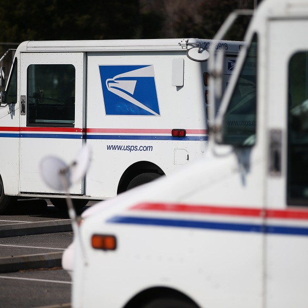 U.S. Postal Service mail trucks sit in a parking lot at a distribution center in San Francisco on Feb. 18, 2015. (Justin Sullivan / Getty Images)