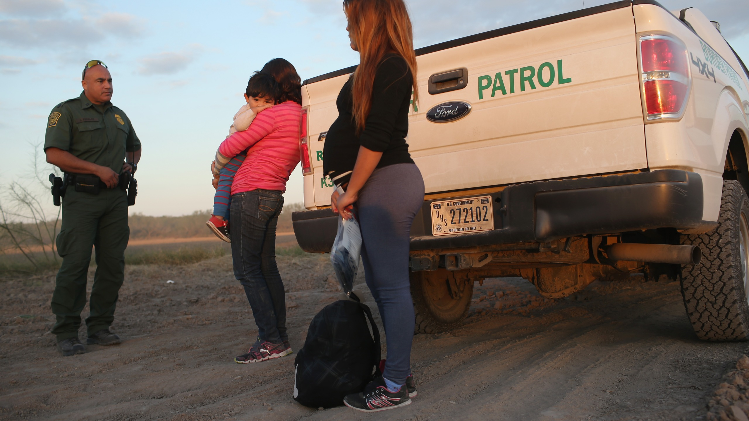 A seven-month pregnant immigrant from El Salvador stands next to a U.S. Border Patrol truck after she and others turned themselves in to border agents on Dec. 7, 2015 near Rio Grande City, Texas.(Credit: John Moore/Getty Images)