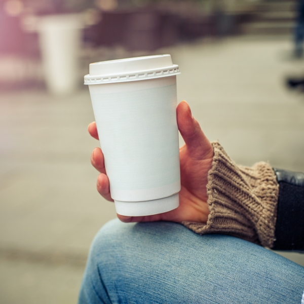 A person drinks coffee in a paper cup in this file photo. (Credit: Getty Images)