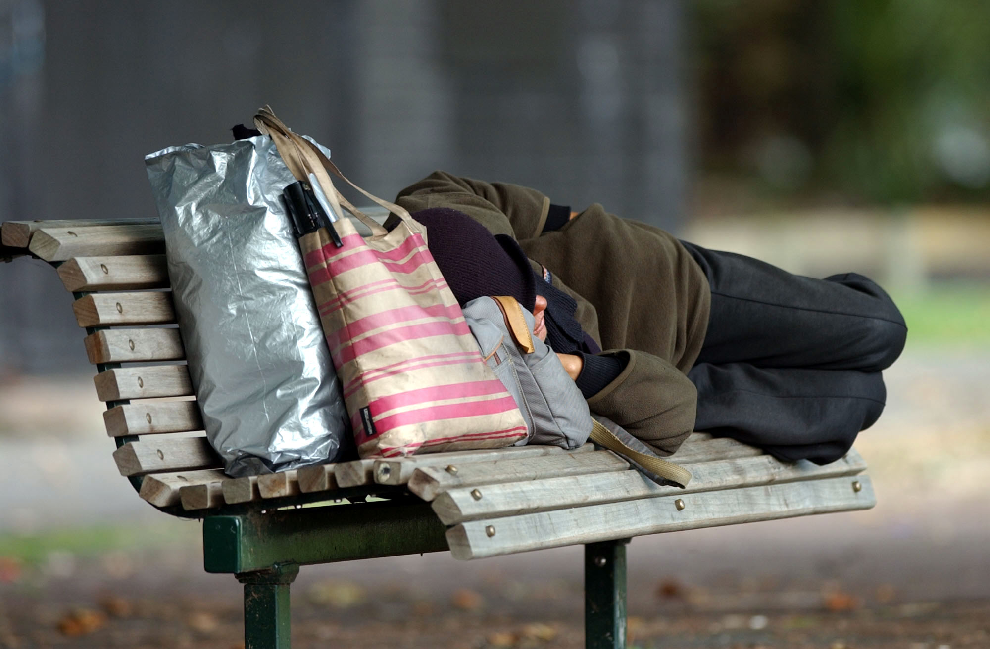 A homeless person sleeping on a park bench. (Credit: Dean Purcell/Getty Images)