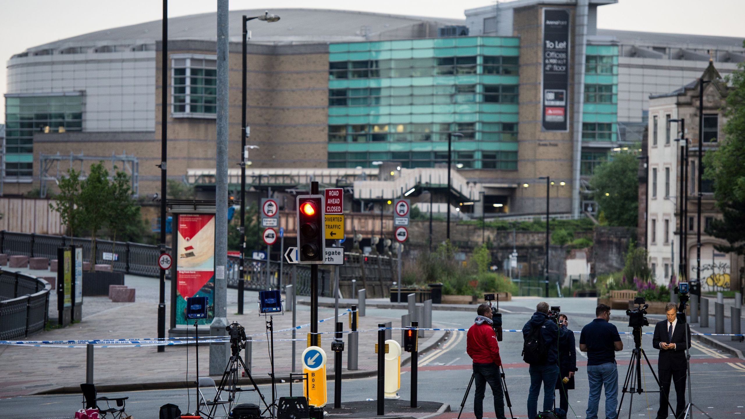 Journalists and television cameras stand by a police cordon near to the Manchester Arena in Manchester, northwest England on May 24, 2017, following the May 22 terror attack at the Manchester Arena. (Credit: CHRIS J RATCLIFFE/AFP/Getty Images)