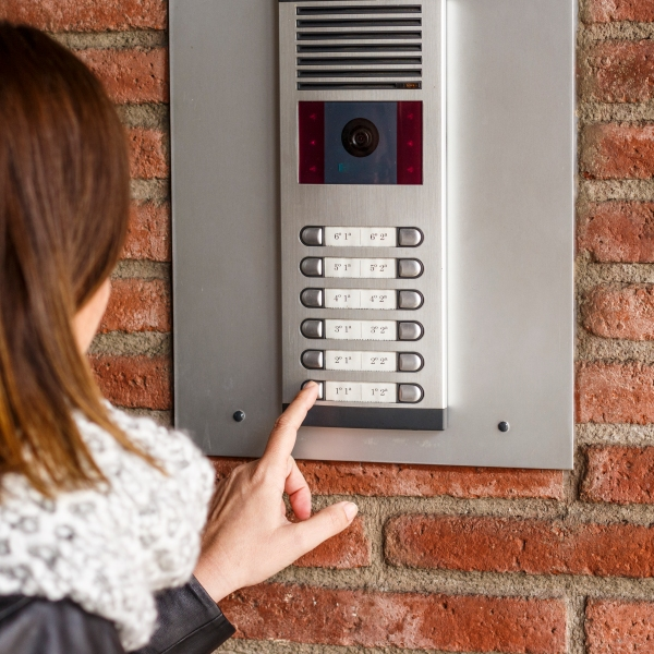 This file photo shows a woman facing a camera in an intercom panel outside a building.(Credit: iStock / Getty Images Plus)