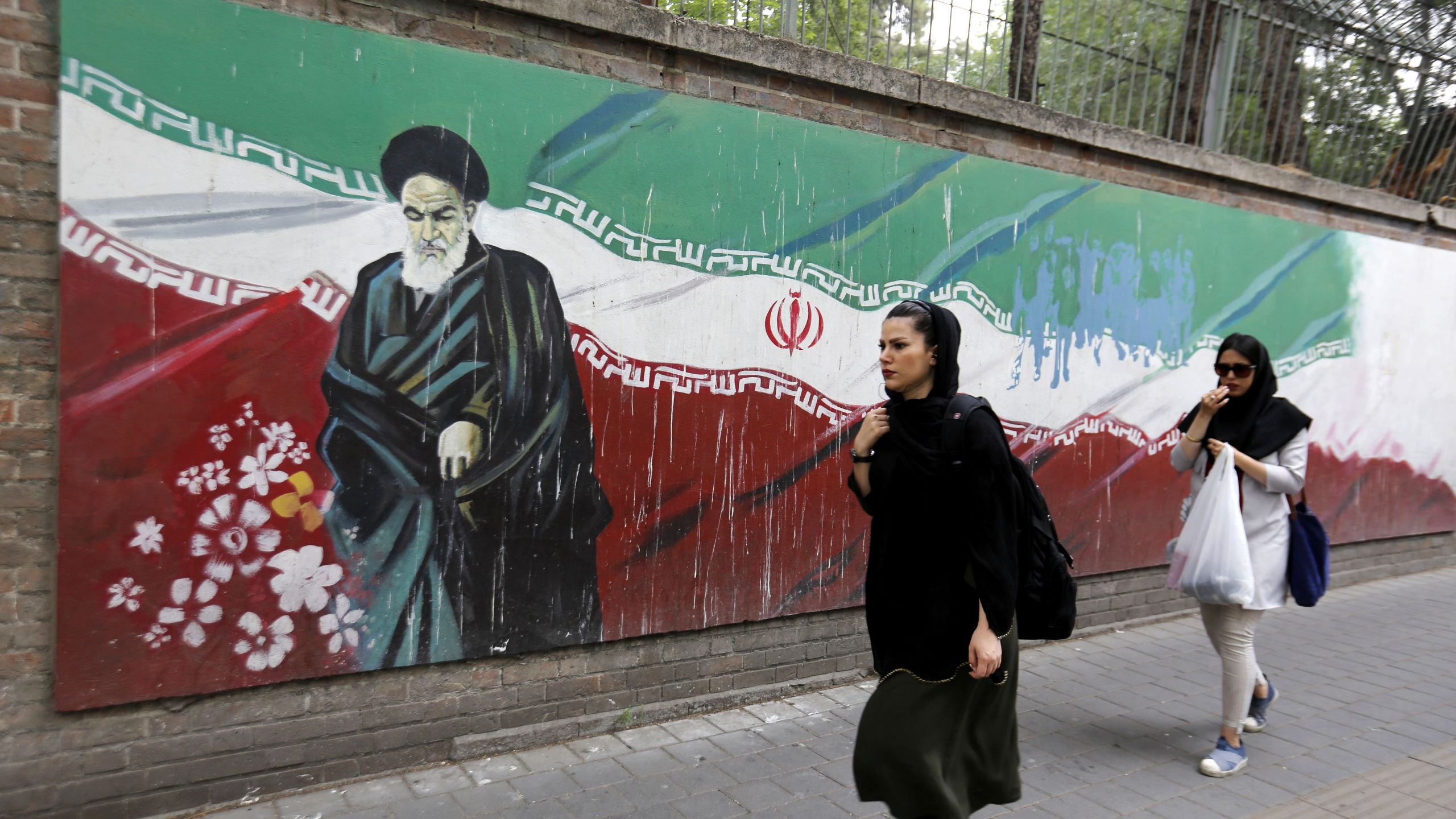 An Iranian woman walks past a mural on the wall of the former US embassy in the Iranian capital Tehran on May 8, 2018. (Credit: ATTA KENARE/AFP/Getty Images)