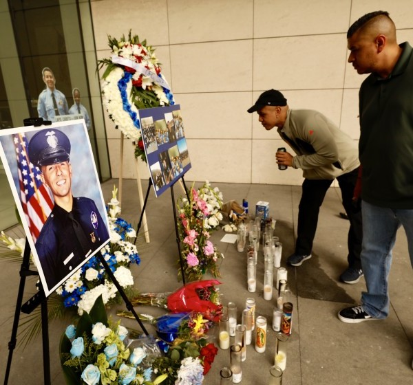 Chris Martin, center, and Ricardo Camacho visit a memorial to slain LAPD officer Juan Jose Diaz in front of LAPD headquarters in July 2019. Camacho's parents were godparents to Diaz. (Credit: Al Seib / Los Angeles Times)
