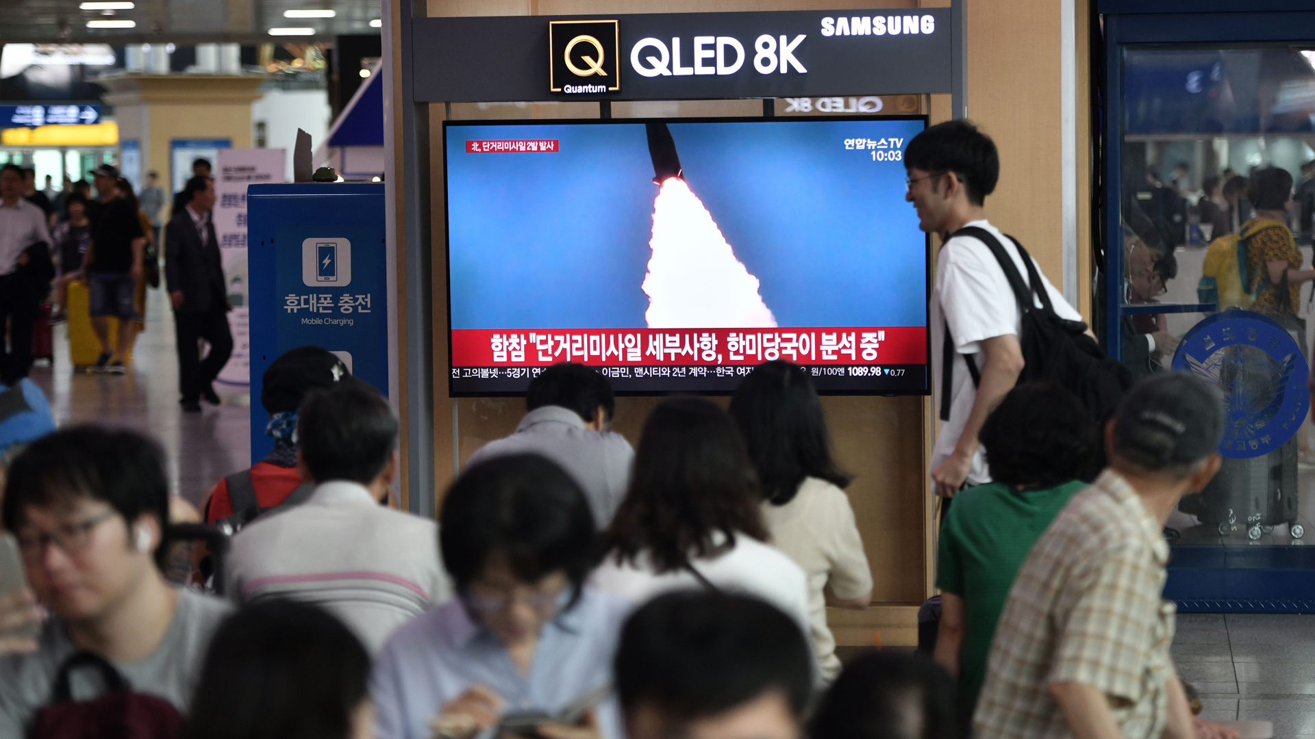 People watch a television news screen showing a file footage of a North Korean missile launch, at a railway station in Seoul on July 25, 2019. (Credit: Jung Yeon-Je/AFP/Getty Images)