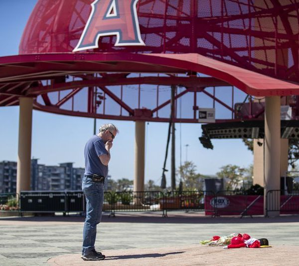 After placing a bouquet of flowers for Tyler Skaggs down in front of Angel Stadium, Angels fan Bob Horan spends a quiet moment by himself on July 1, 2019. (Credit: Allen J. Schaben / Los Angeles Times)