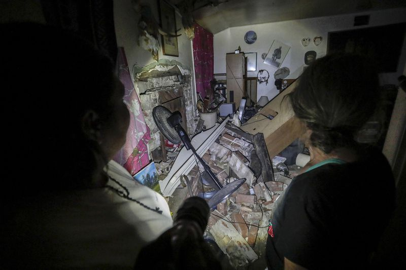 An emergency response team member walks with a Trona resident as she sorts through the rubble of her home on July 6, 2019. (Credit: Robert Gauthier / Los Angeles Times)