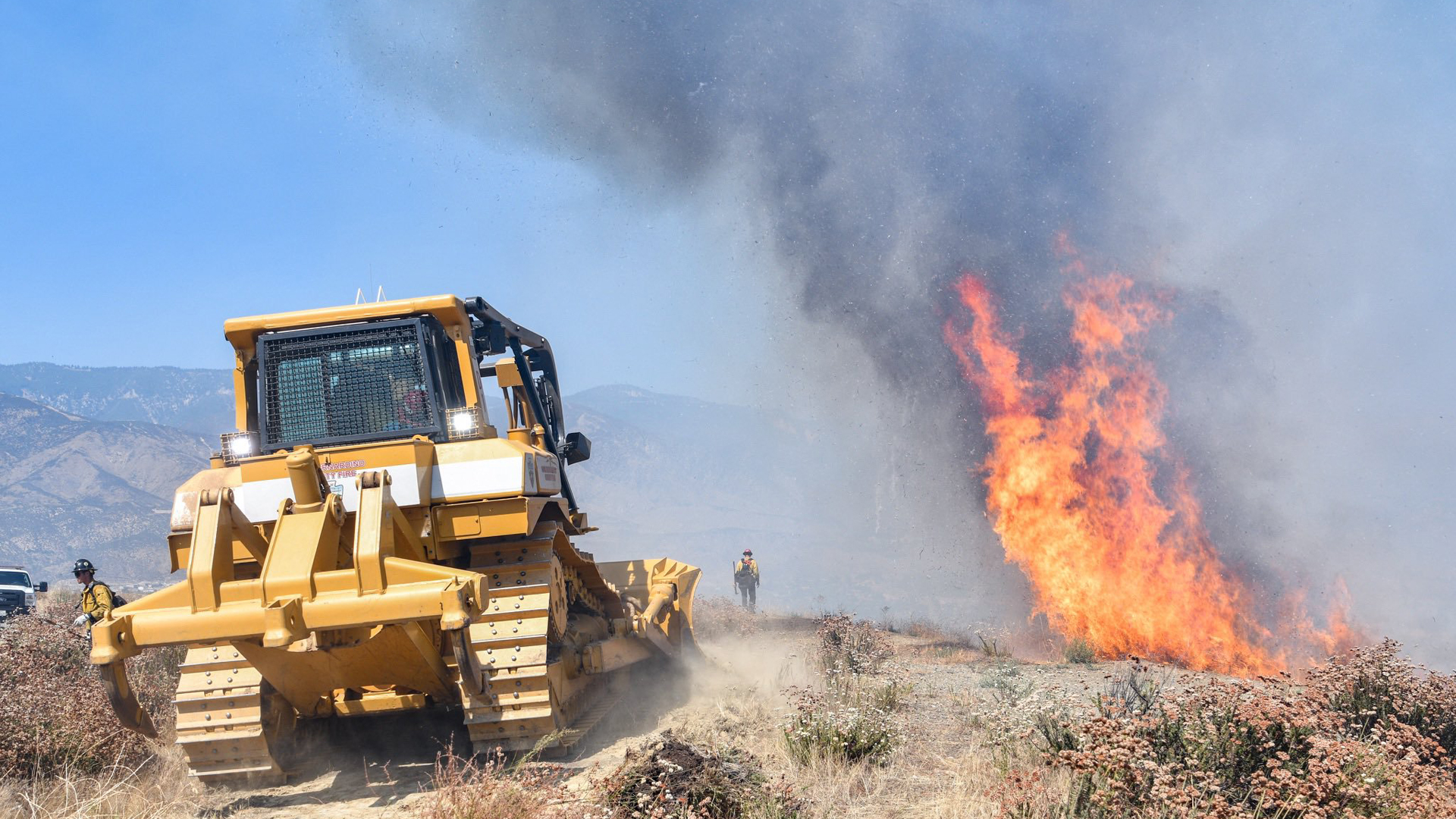 Crews use a bulldozer as they battle a brush fire in San Bernardino on July 31, 2019, in an image released by the San Bernardino County Fire Department.