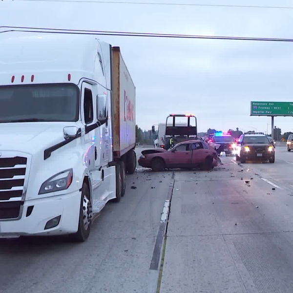 A big rig and a sedan sit on the southbound 605 Freeway in Norwalk on July 2, 2019. (Credit: KTLA)