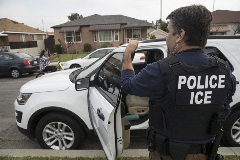 An Immigration and Customs Enforcement fugitive operations team member outside the Montebello home of a Mexican national in Montebello in 2017.(Credit: Brian van der Brug/Los Angeles Times)