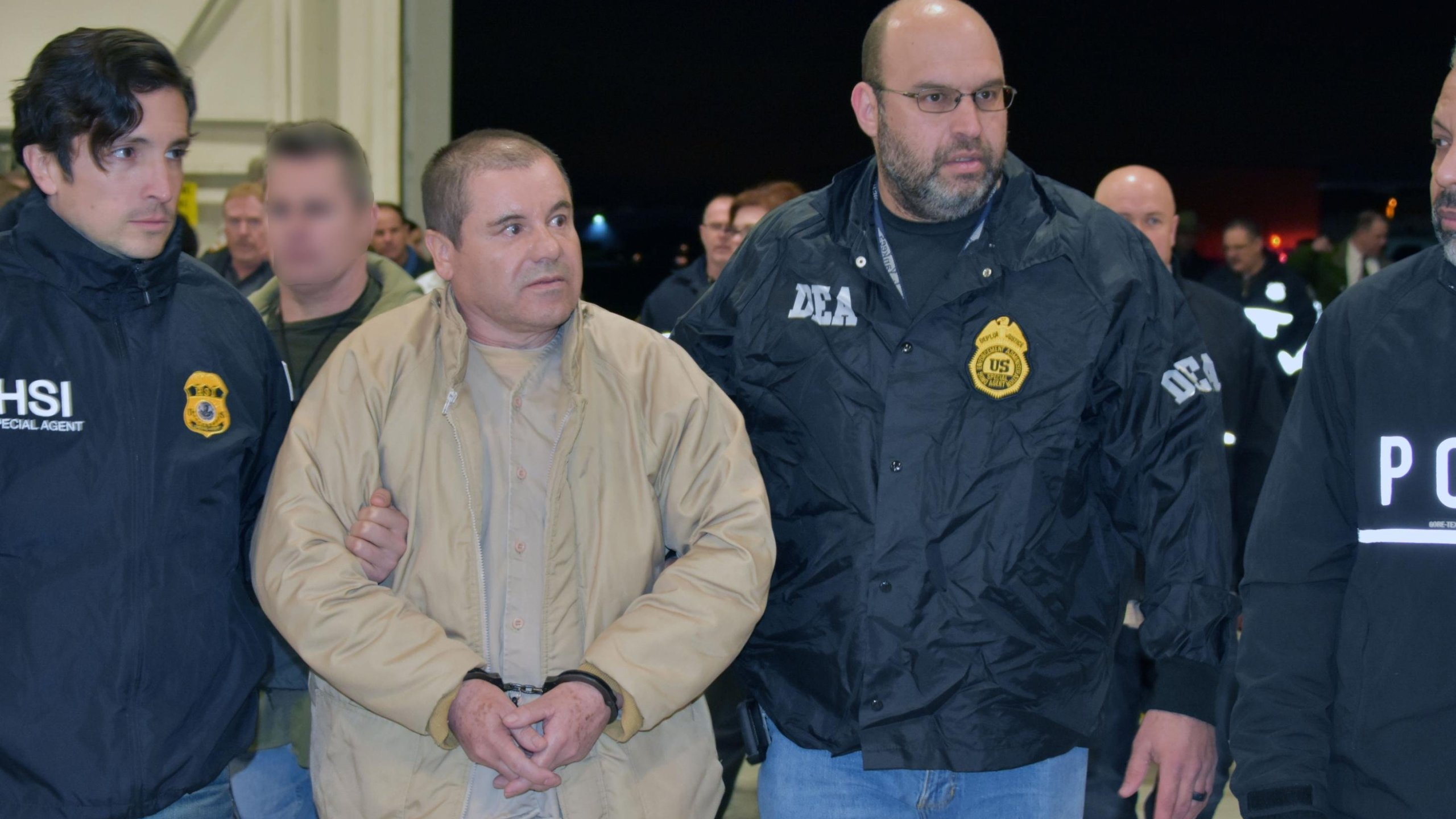 """Convicted drug kingpin Joaquin """"El Chapo"""" Guzman is escorted by federal agents as he's extradited to the U.S. on Feb. 19, 2019, in this handout photo from the Department of Justice."""