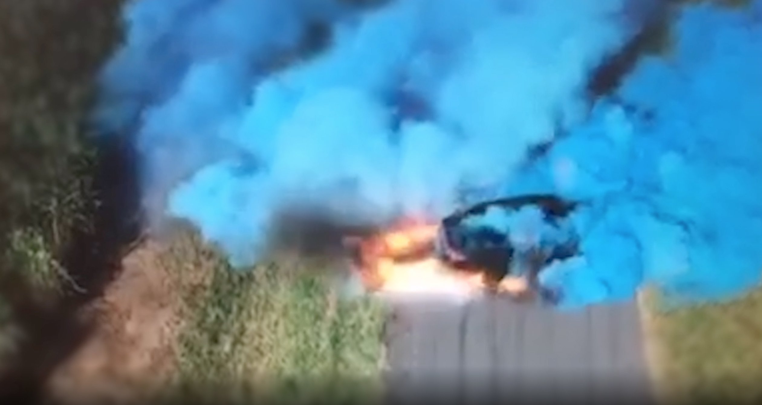 A still from a video released by the Queensland Police Service in July 2019 shows a car emitting blue smoke during a gender reveal party.