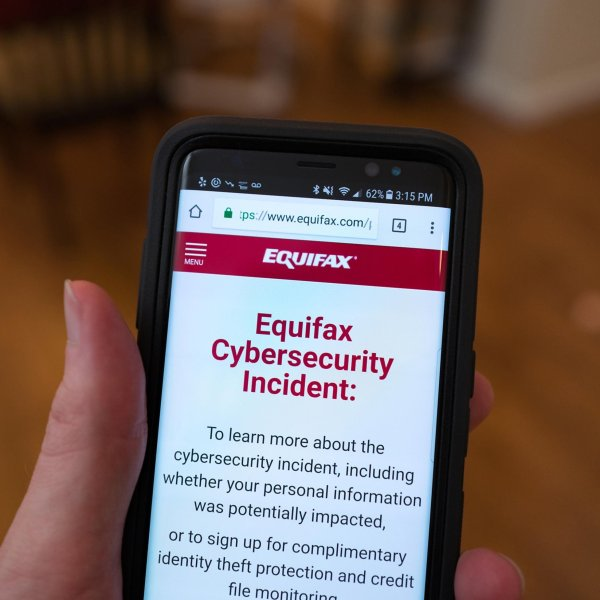 A man holds a mobile phone open to the website of credit bureau Equifax in San Ramon on Sept. 28, 2017. (Credit: Smith Collection / Gado / Getty Images)
