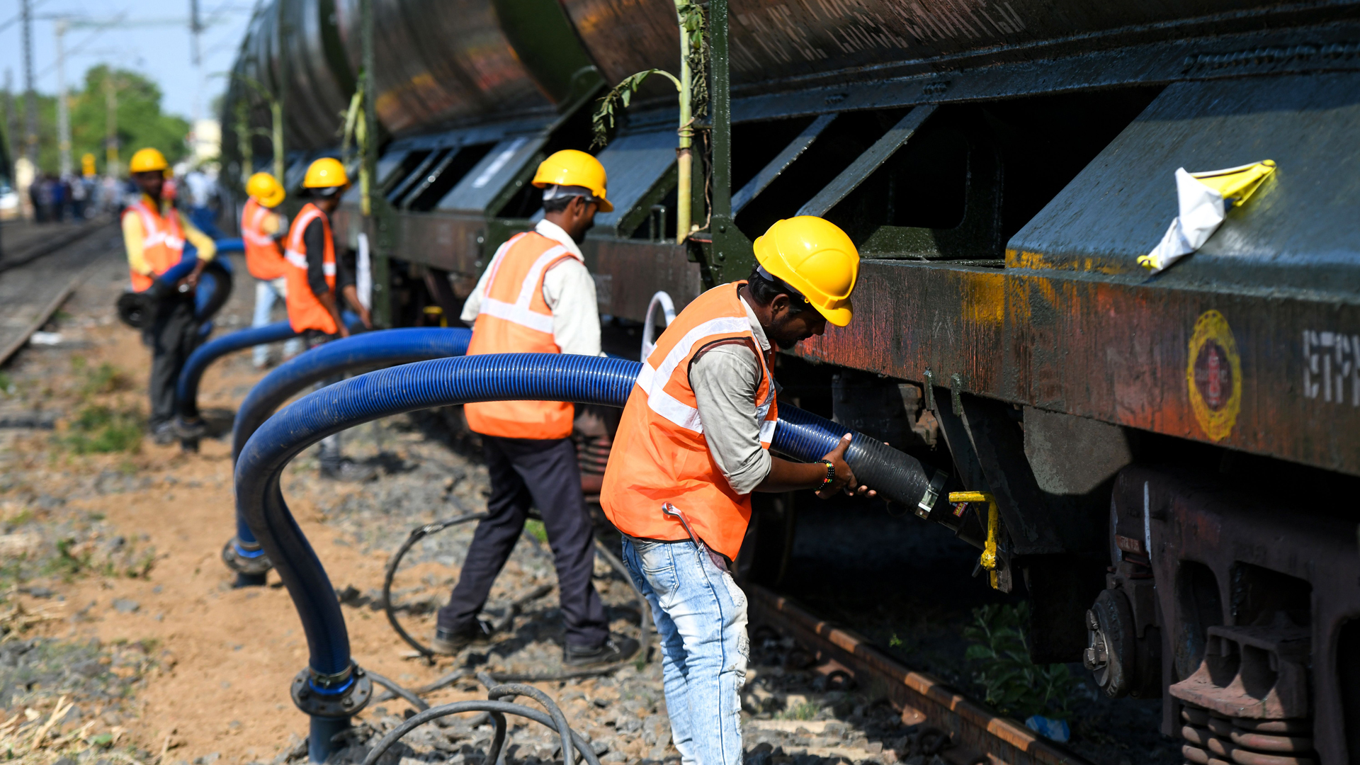 Indian laborers connect pipes to collect water from a special train of 50 wagons carrying liters of water at Villivakkam railway station in Chennai on July 12, 2019.(Credit: Arun Sankar/AFP/Getty Images)