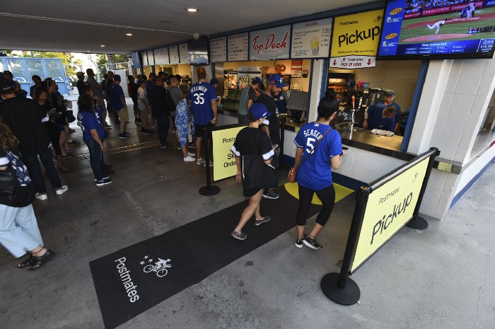 Fans use a designated Postmates pick-up line at Dodger Stadium in this photo provided by the app company.