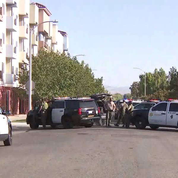 Officers stand outside a Lancaster apartment building where a sniper supposedly opened fire on a deputy on Aug. 21, 2019. The Los Angeles County Sheriff's Department has since said that deputy's report was false. (Credit: KTLA)