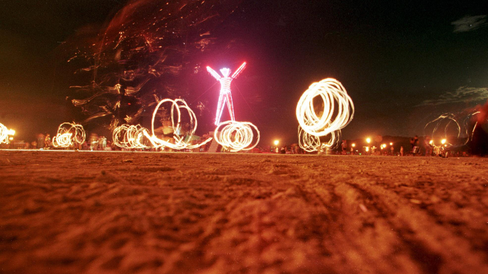 "Dancers at the ""Burning Man"" festival create patterns with fireworks in the Black Rock Desert of Nevada just prior to burning a five-story, neon-lit effigy of a man on the last night of the week-long festival in September 2006. (Credit: MIKE NELSON/AFP/Getty Images)"