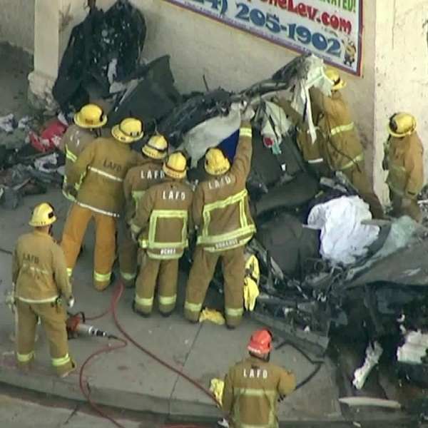 Firefighters investigate the wreckage of a car that was demolished, killing the driver, after the vehicle crashed into a building in the Pico-Robertson area on Aug. 29, 2019. (Credit: KTLA)