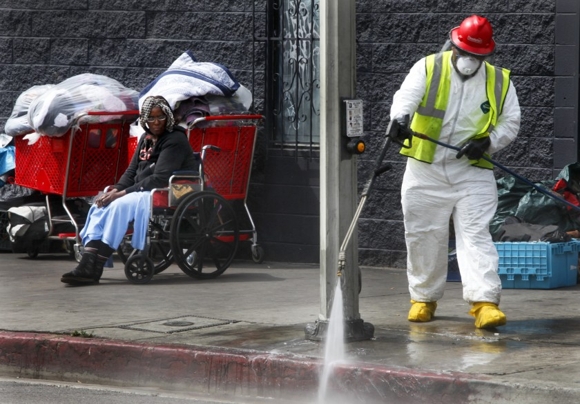 A Los Angeles city sanitation worker sprays the sidewalk during a cleanup on skid row in this undated photo. (Credit: Mark Boster / Los Angeles Times)