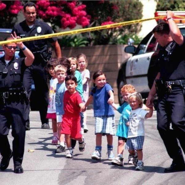 Children from the Jewish Community Center in Granada Hills are escorted to safety by LAPD officers on Aug. 10, 1999. (Credit: Myung J. Chun/Los Angeles Times)