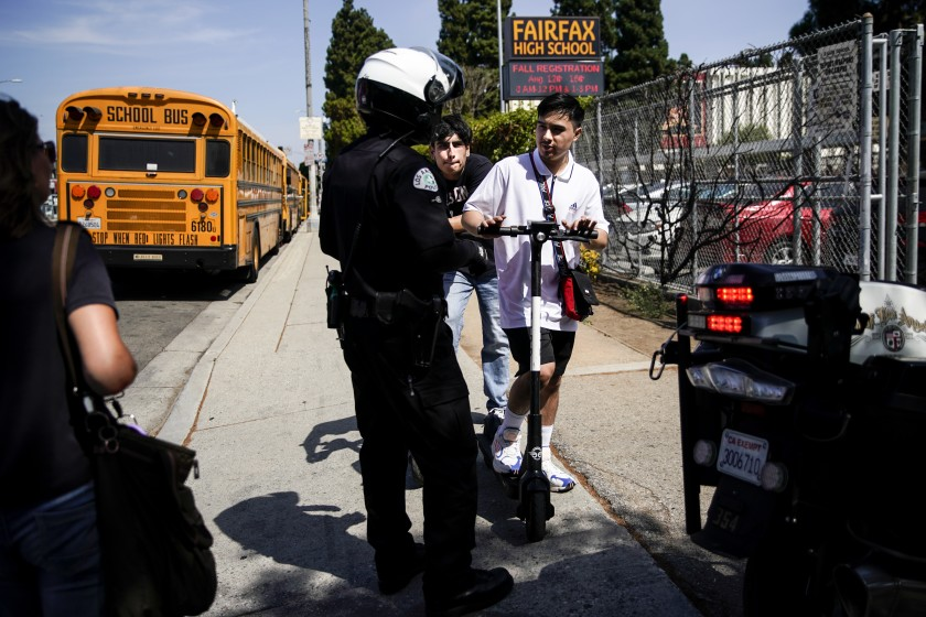 An LAPD bike officer warns two young men about riding their e-scooters on the sidewalk, in front of Fairfax High School in Los Angeles on Aug. 22, 2019.(Credit: Kent Nishimura/Los Angeles Times)