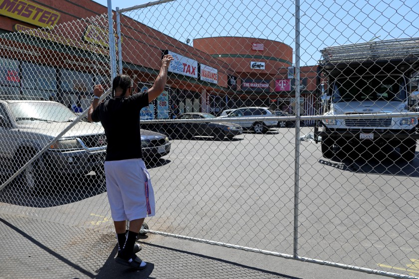 Workers install a fence on Aug. 1, 2019, outside the lot in South Los Angeles where rapper and activist Nipsey Hussle was killed in March.(Credit: Gary Coronado / Los Angeles Times)