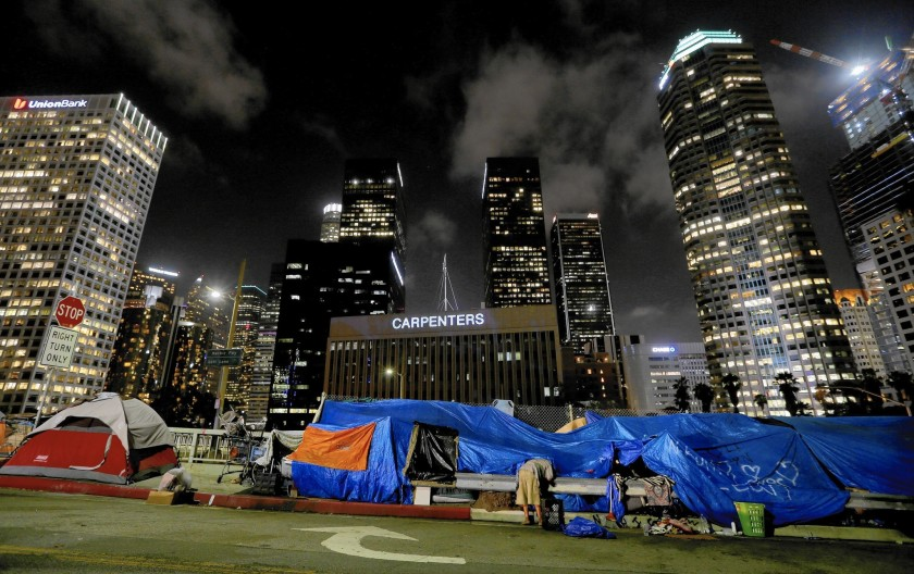 A homeless man prepares to sleep for the night in an encampment beneath the gleaming towers of the Financial District in downtown Los Angeles in this undated photo.(Credit: Luis Sinco / Los Angeles Times)