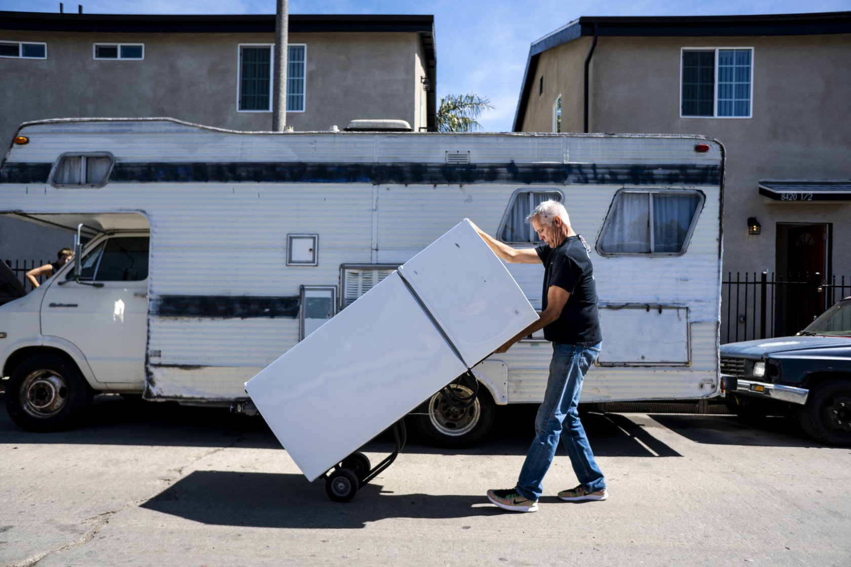 John Betz rolls a refrigerator down a street in South Los Angeles for a duplex he and his partner, Heidi Roberts, set up to house homeless people in this undated photo. (Credit: Kent Nishimura / Los Angeles Times)