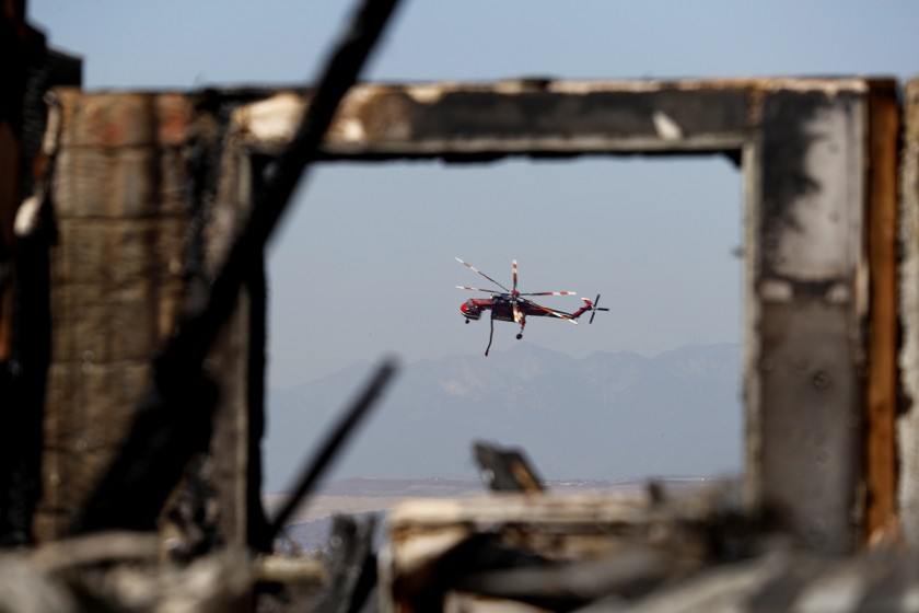A water-dropping fire helicopter is framed through a burnt structure during the Canyon Fire in Anaheim Hills. (Credit: Allen J. Schaben/Los Angeles Times)