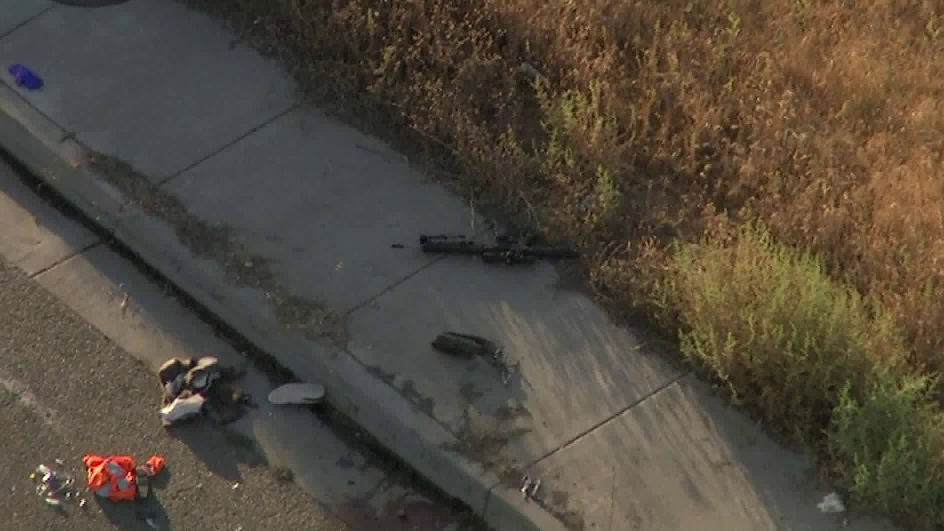 A firearm is seen on the ground at the scene of a shooting that left one CHP officer dead and two other wounded in Riverside on Aug. 12, 2019. (Credit: KTLA)