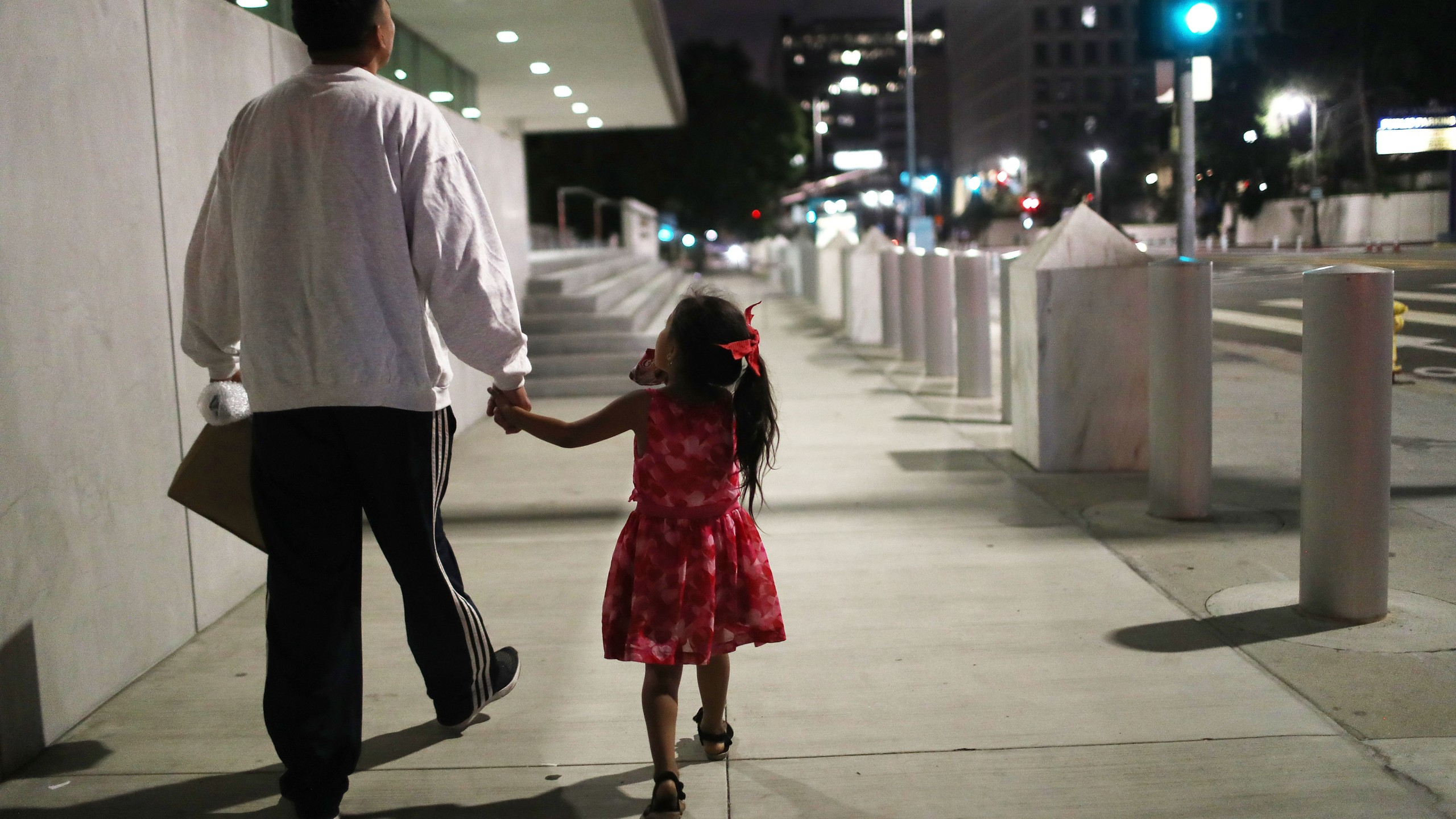 Honduran father Victor walks with his daughter Katie near Metropolitan Detention Center, shortly after he was released on bond from six months in ICE custody, on Oct. 2, 2018, in Los Angeles. (Credit: Mario Tama/Getty Images)