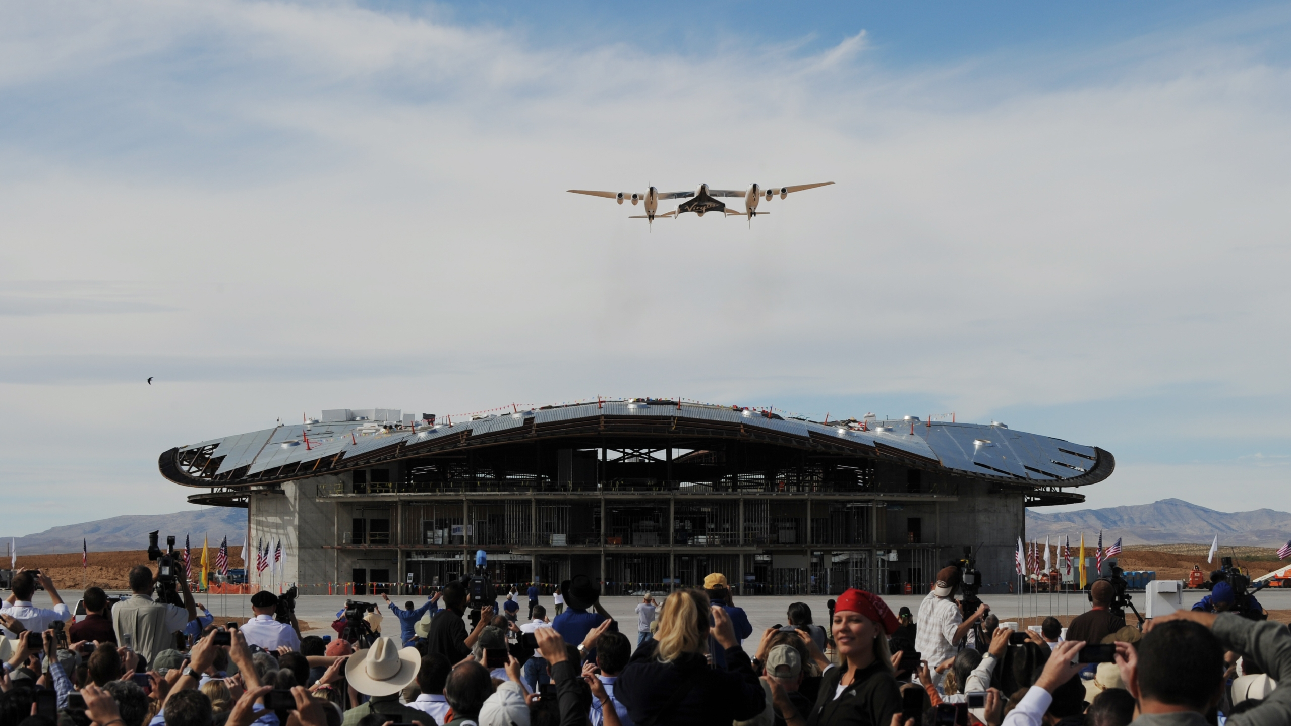 The Virgin Galactic VSS Enterprise spacecraft flies over its hanger before its first public landing during the Spaceport America runway dedication ceremony near Las Cruces, New Mexico on October 22, 2010. (Credit: MARK RALSTON/AFP/Getty Images)