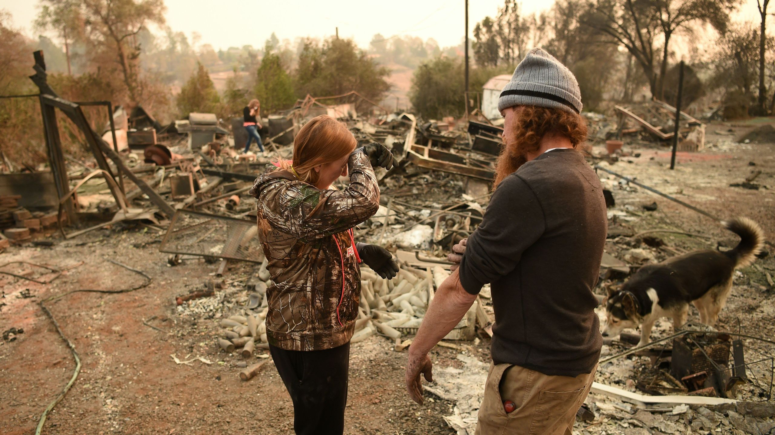 Kimberly Spainhower and her husband Ryan Spainhower weep while searching through the ashes of their burned home in Paradise, California on Nov. 18, 2018. (Credit: JOSH EDELSON/AFP/Getty Images)